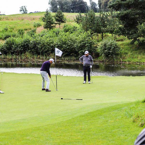 Golfbane med 4 golfspillere der putter